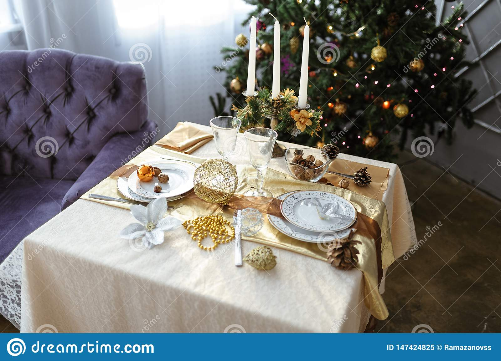 Decorated table with candles and white tablecloth on the background of a decorated Christmas tree