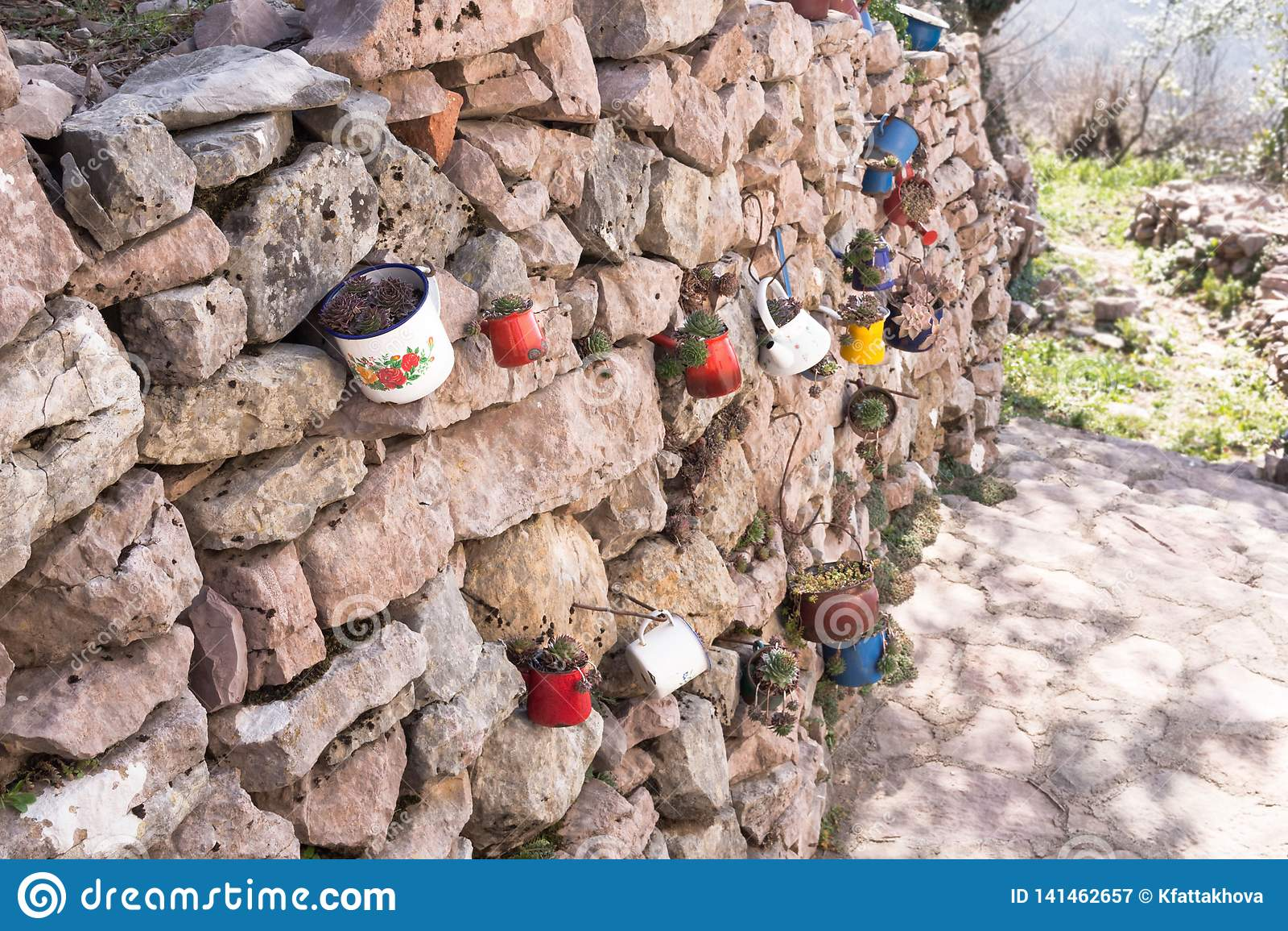 Decoratie van de steenmuur van de tuin met ijzermokken, ijzerwerktuigen met bloemen Zonnige dag