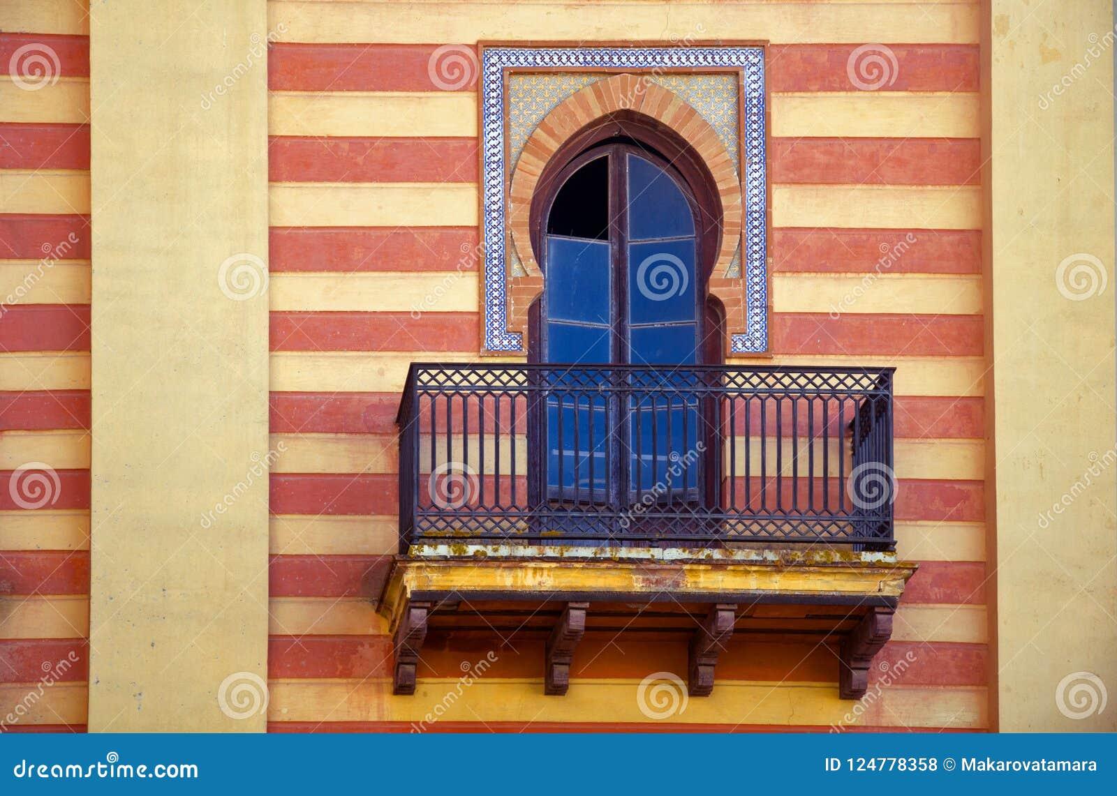 Decoratief venster in Spaanse stijl op de gestreepte muur