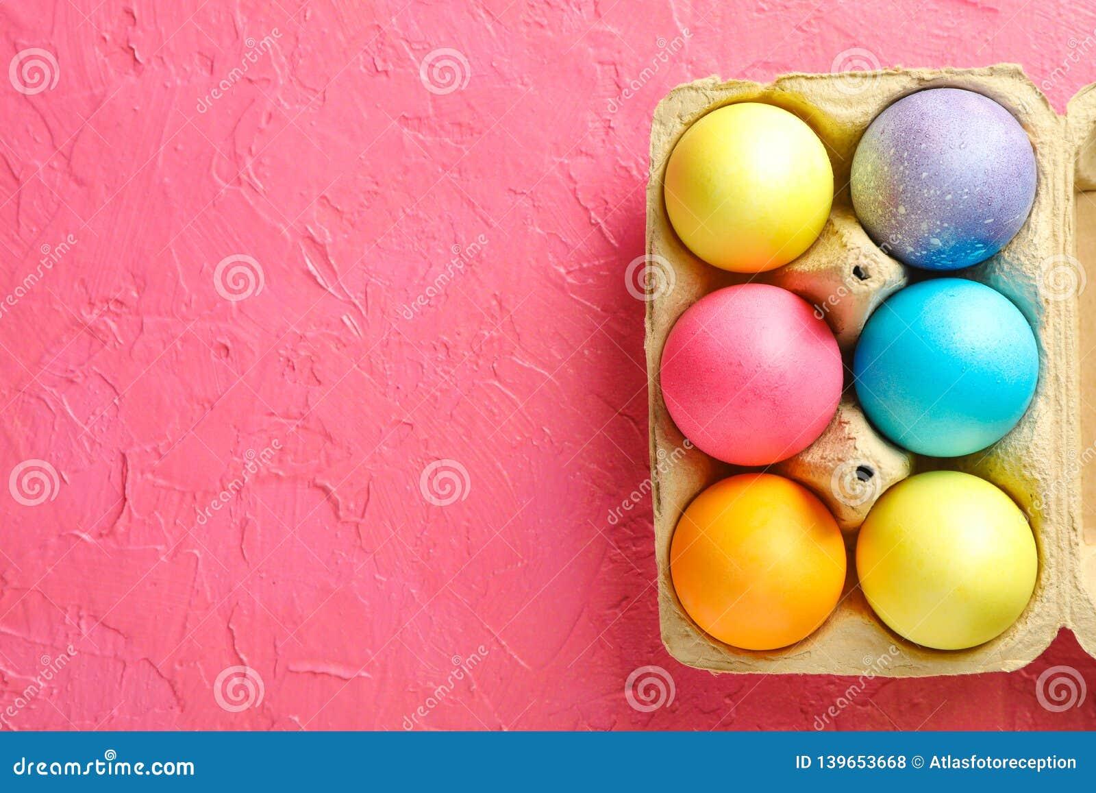 Decoratieve eieren in kartonvakje op kleurenachtergrond, ruimte voor tekst
