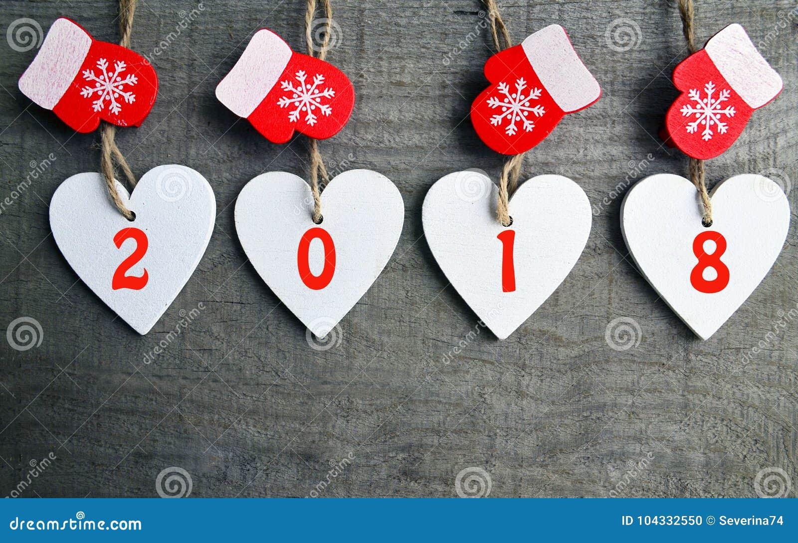 Decoratieve witte houten Kerstmisharten en rode vuisthandschoenen met 2018 aantallen op houten achtergrond met exemplaarruimte Ge