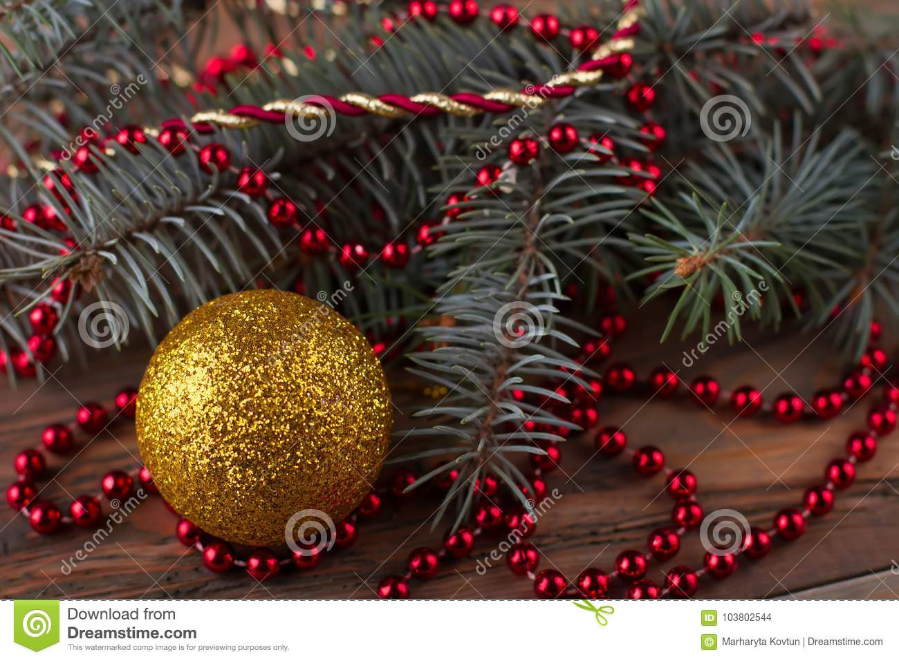 decorating a christmas tree with ornaments glittering yellow bauble and red bead garland on fir branch