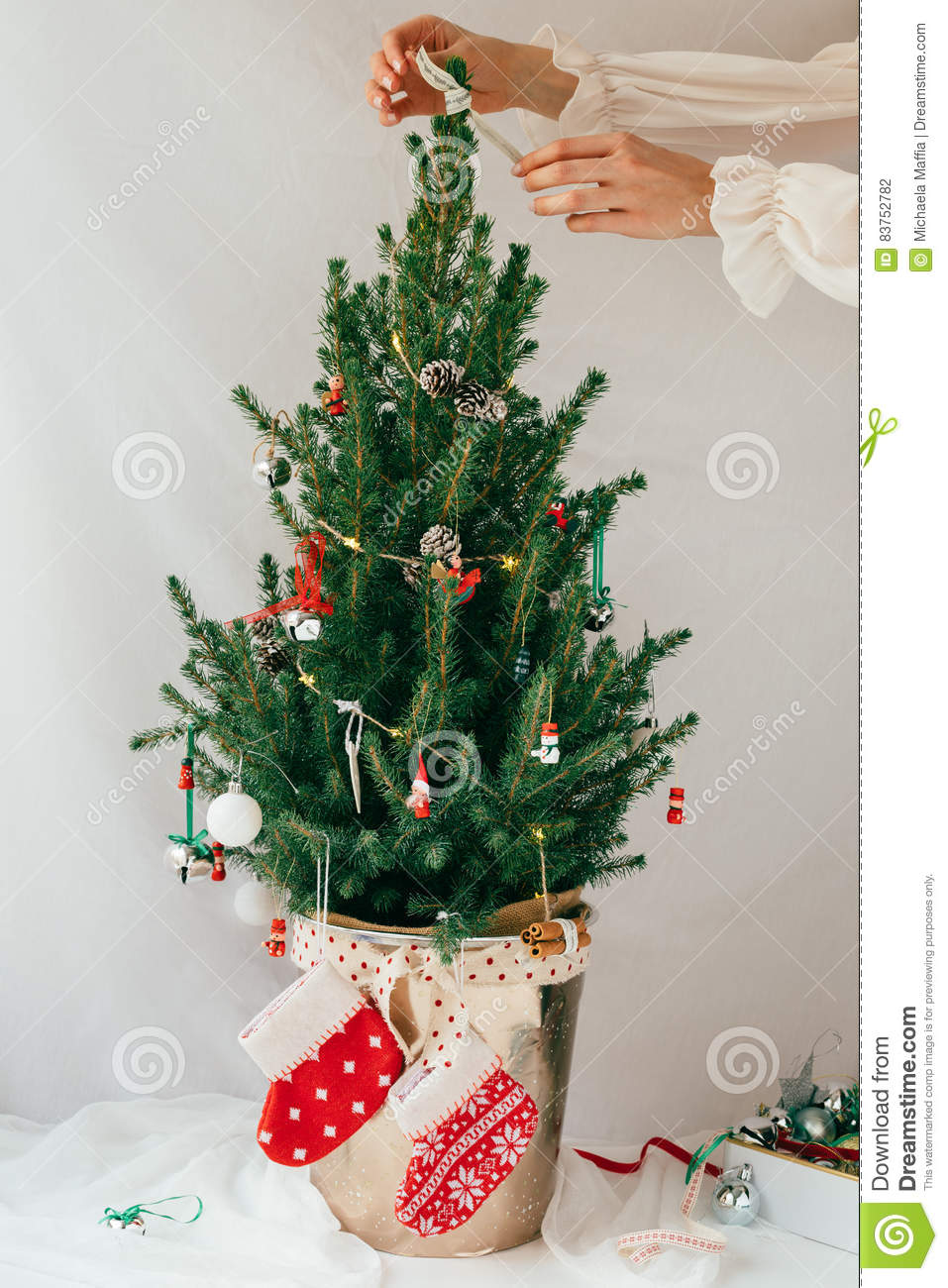 vertical festive scene of a natural fir christmas tree decorated with wooden decorations and baubles with female adding a ribbon to the top