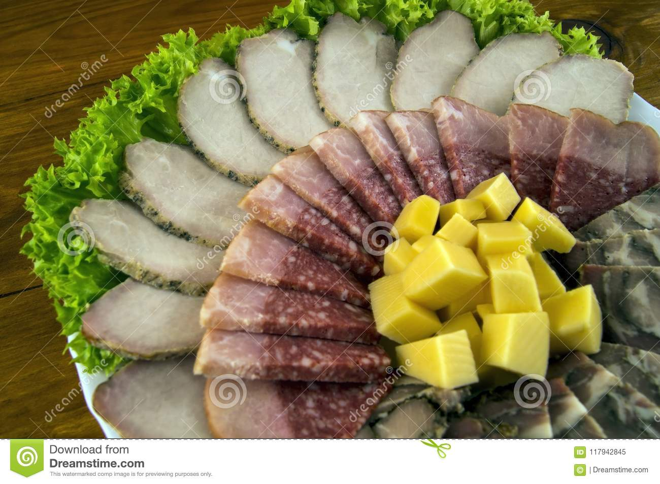 Decoration of sausage, meat, rolls and cheese with lettuce leaves on a white plate