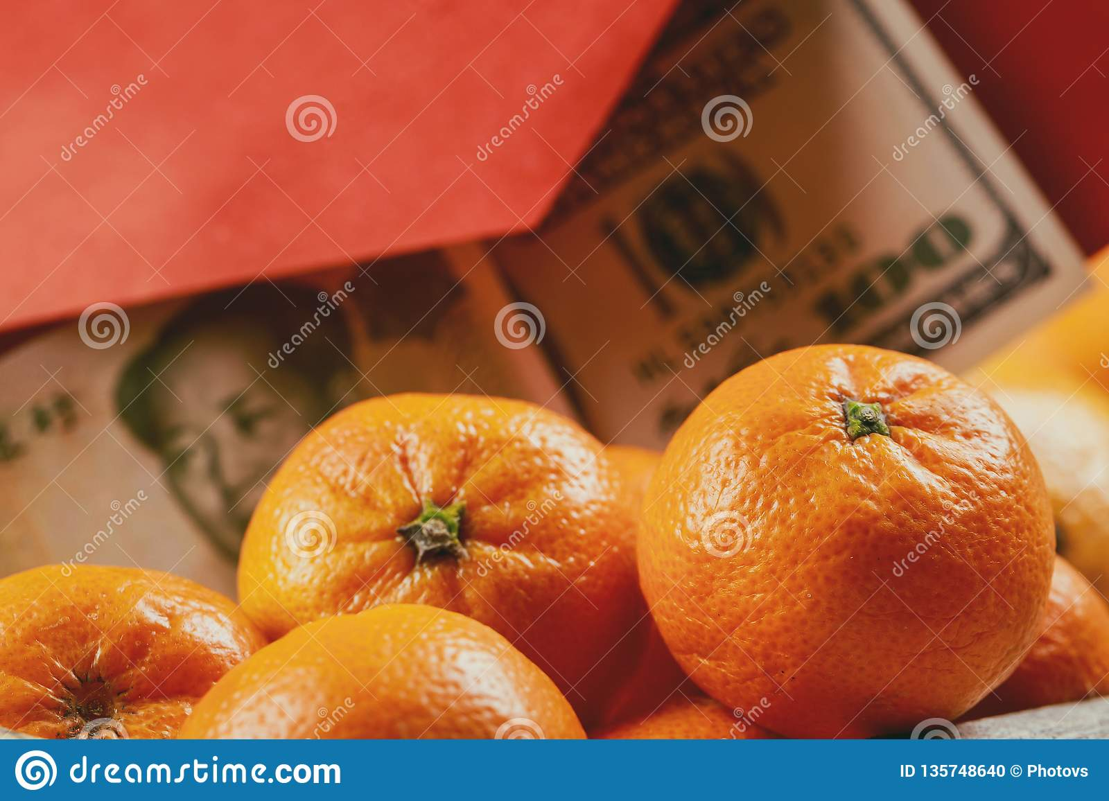 Overhead of top decorations Chinese New Year festive mandarine oranges background concept Chinese Yuan bills vs U.S. dollar