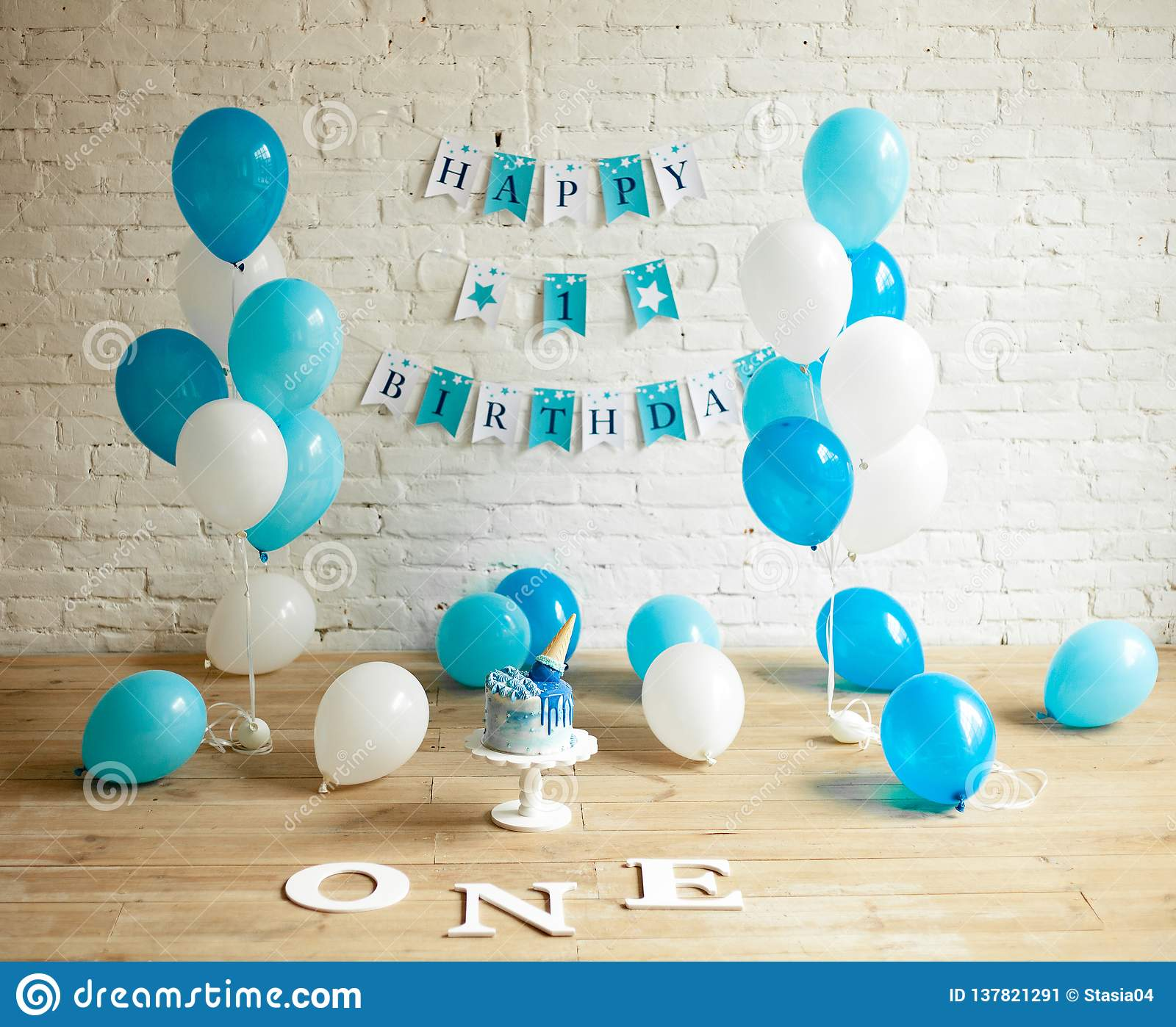 Decorations for one year birthday with balloons, cake and inscriptions on wall and floor