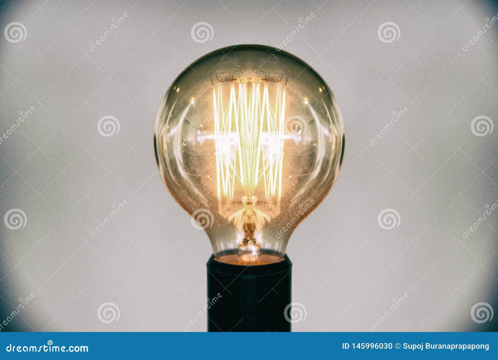 Decorative antique edison style light bulb.Beautiful retro luxury light lamp decor glowing selective focus film grain style effect