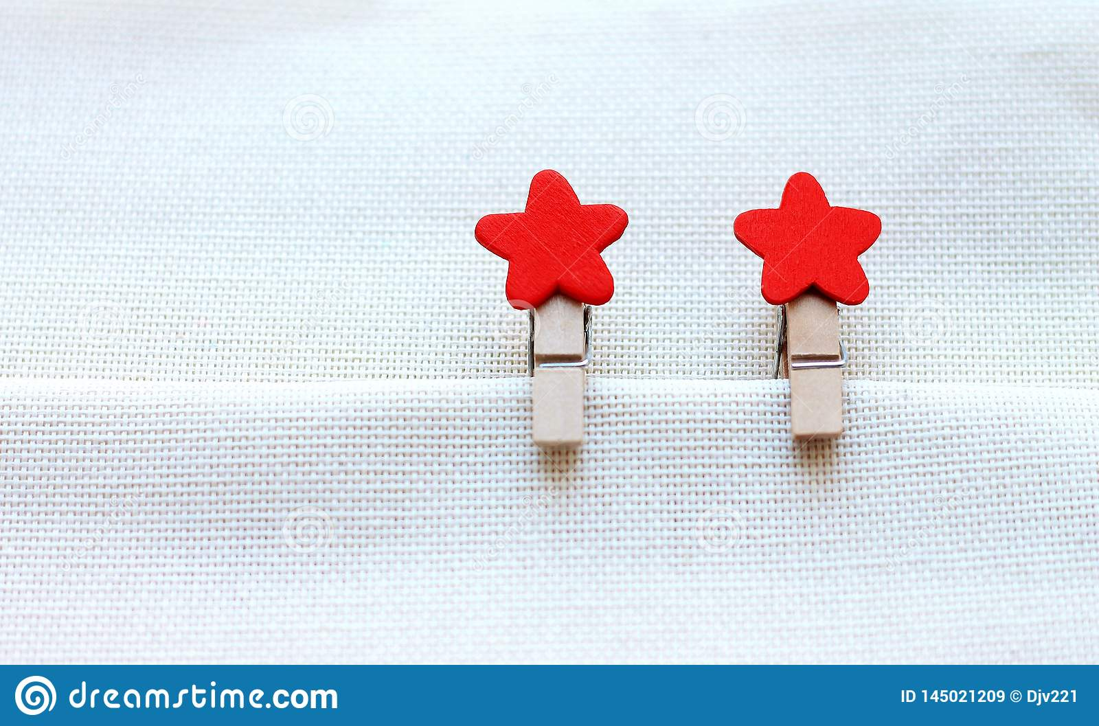 Decorative clothespins with red stars on bright cloth