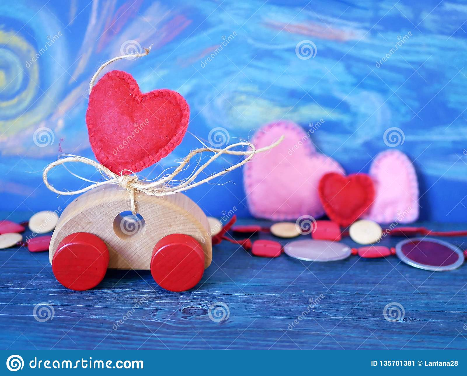 Decorative composition of a toy car and a heart made of felt on the background of pastel drawing, romantic decor on a blue wooden