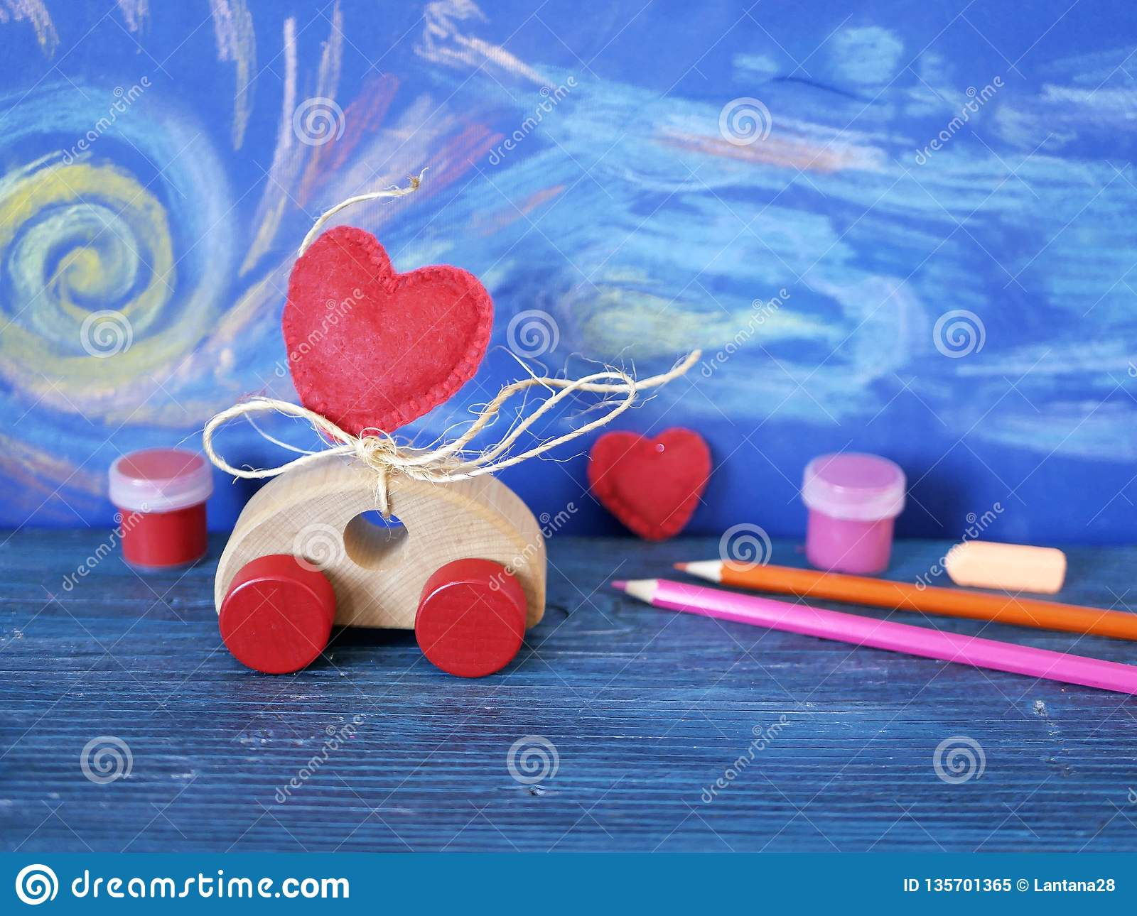 Decorative composition of a toy car and a heart made of felt, paints and pencils on the background of pastel drawing, the concept