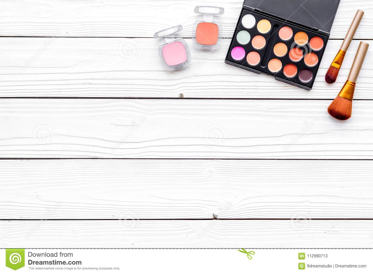 Decorative cosmetics set with eyeshadow, rouge, brushes on white desk background top view copy space