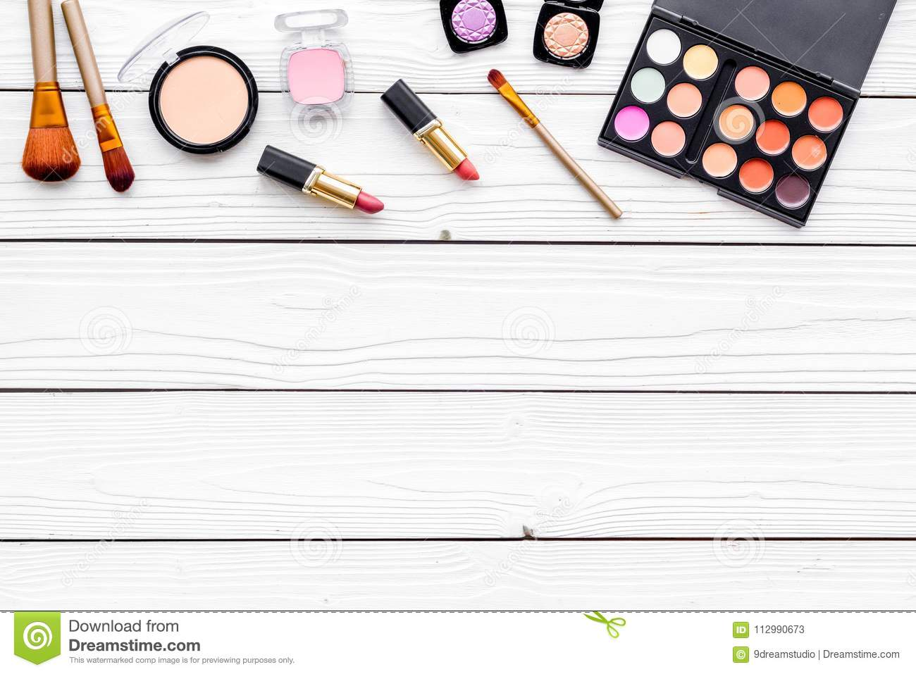 Decorative cosmetics set with eyeshadow, rouge, lipstick, brushes on white desk background top view copy space