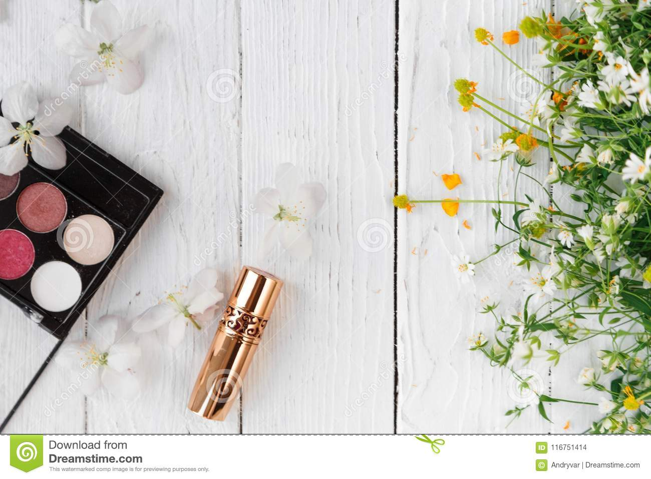 Fresh flowers, decorative cosmetics on a wooden background
