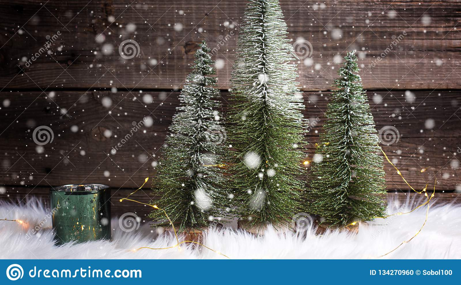 Decorative fir trees, green candleholder and fairy lights on white fur background against vintage wooden wall