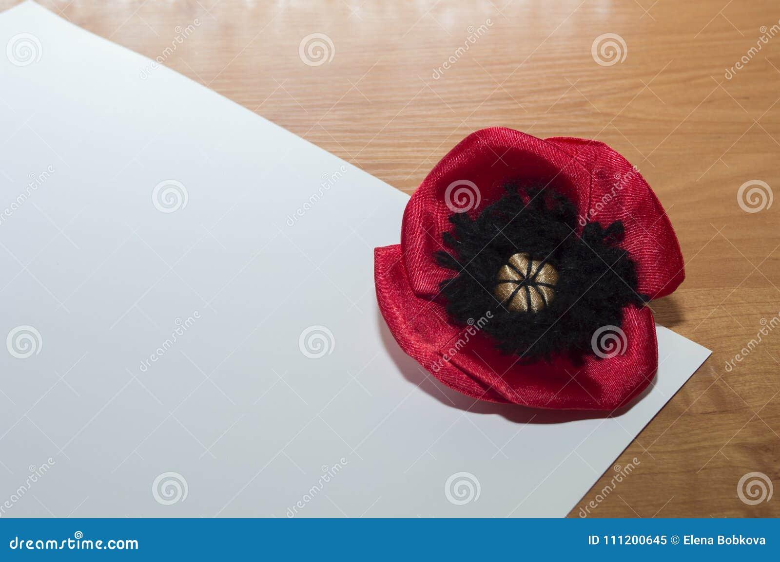 Decorative red poppy flower made satin fabric lies on a white download decorative red poppy flower made satin fabric lies on a white sheet of paper mightylinksfo