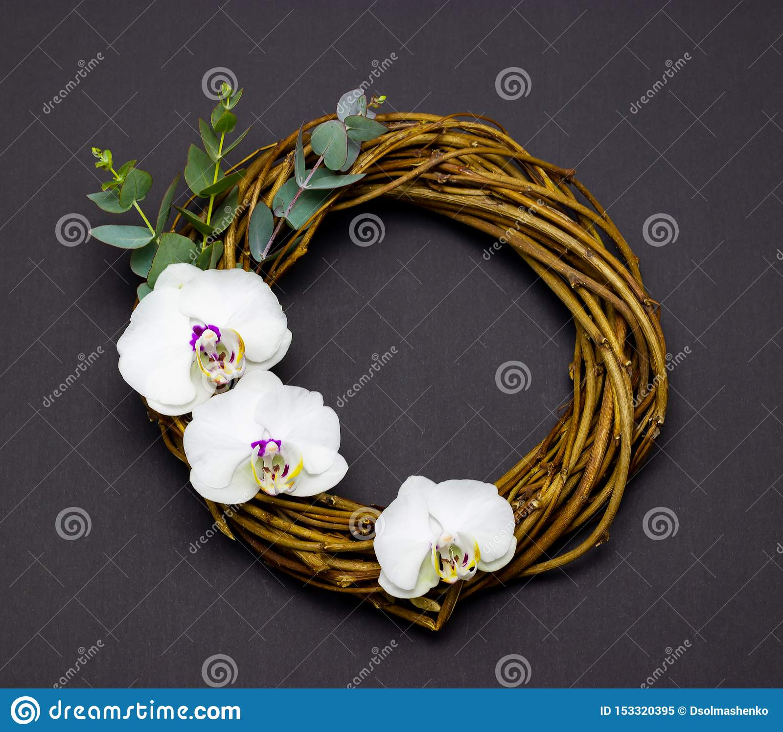 Decorative round wreath with orchid flowers and eucalyptus on a dark background