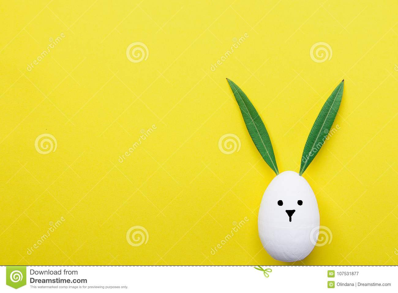 Decorative White Painted Easter Egg Bunny with Drawn Cute Kawaii Face. Green Leaves as Ears. Pastel Yellow Background. Spring
