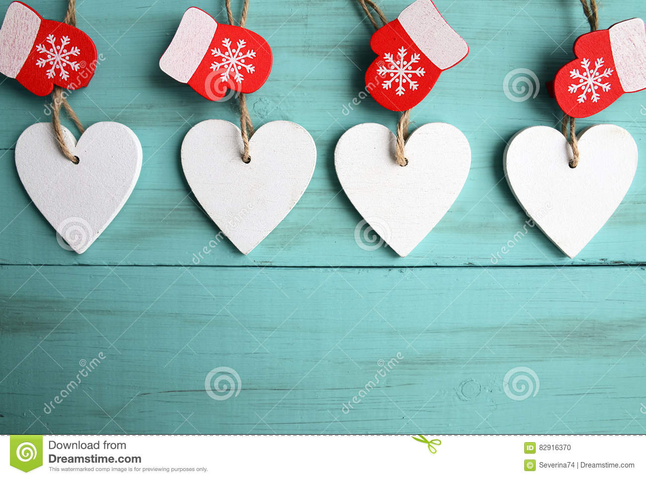 Decorative white wooden Christmas hearts and red mittens on blue wooden background with copy space.