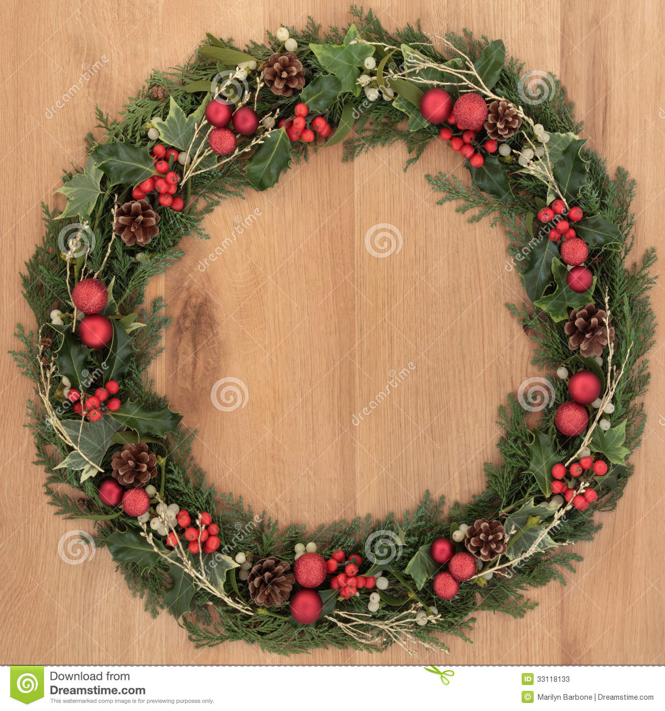 christmas wreath with red bauble decorations holly mistletoe ivy pine cones and cedar over oak background