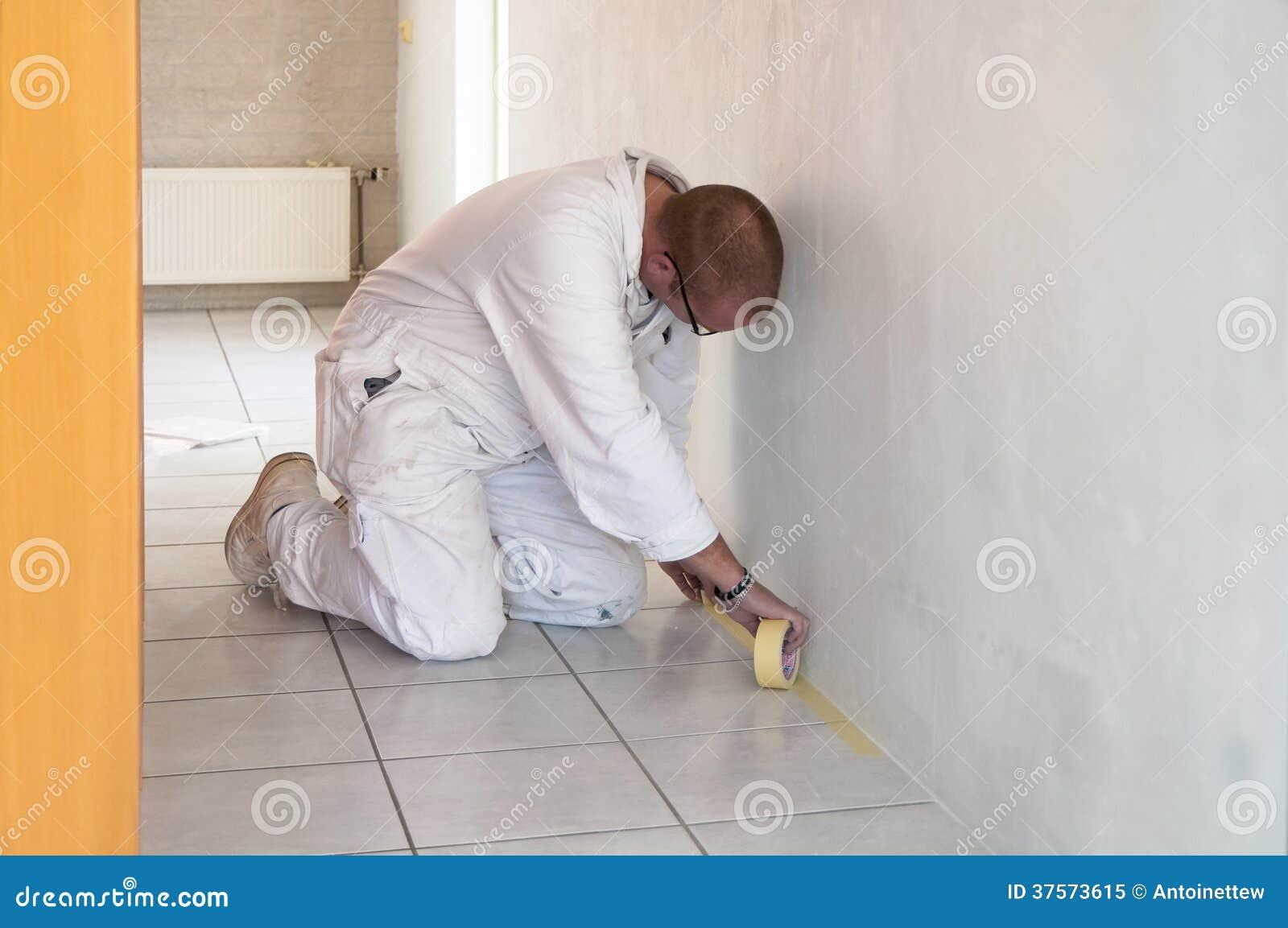 Decoratore domestico inginocchiato occupato con nastro adesivo delle