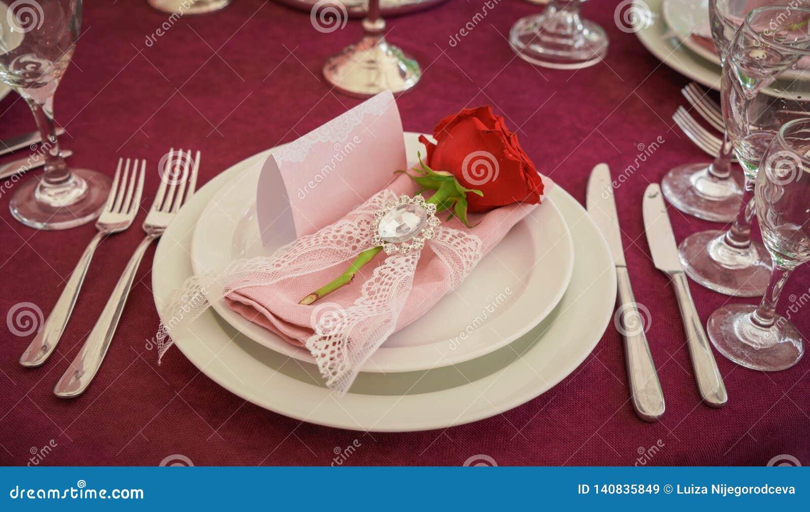 Decorazione festiva della tavola con i fiori rossi