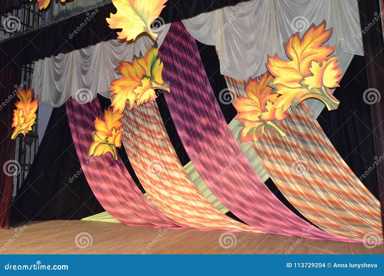 Decorazione in scena che consiste dei panni di Borgogna decorati con le foglie gialle