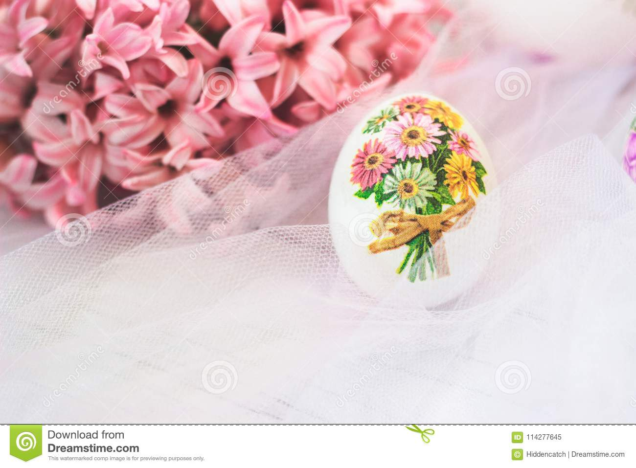 Decoupage decorated Easter egg, with pink hyacinths flowers, on