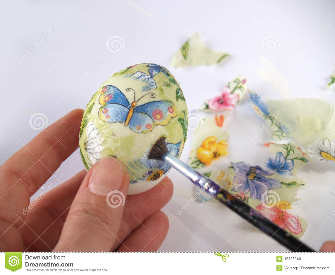Close up of holding and painting Easter egg with decoupage technique.