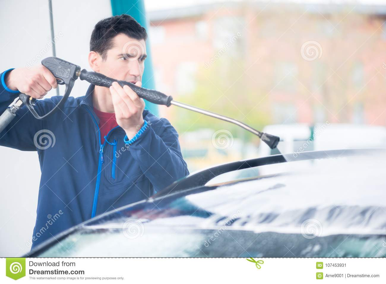 Dedicated worker washing car with high-pressure hose