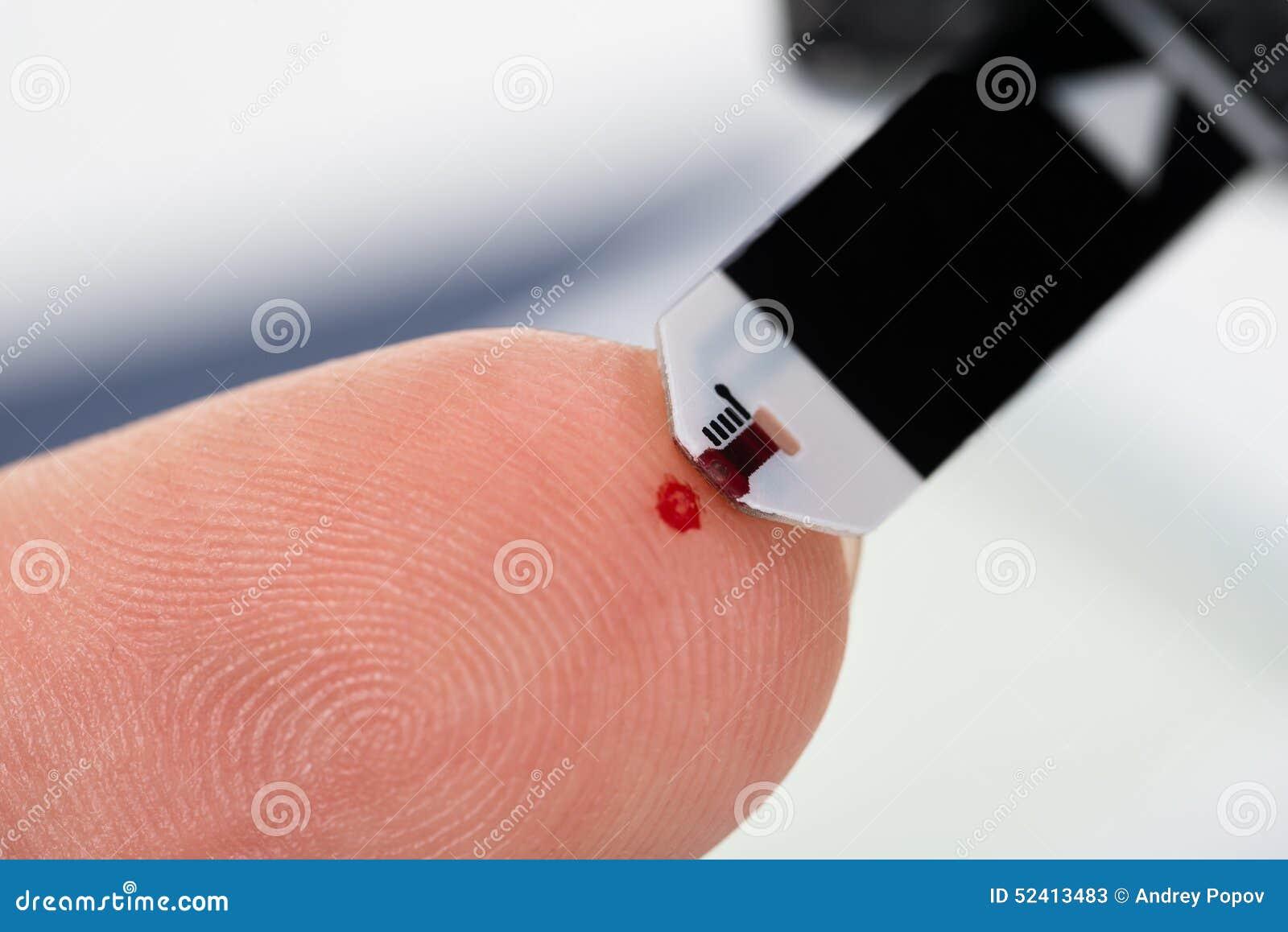 Dedo da pessoa com um glucometer
