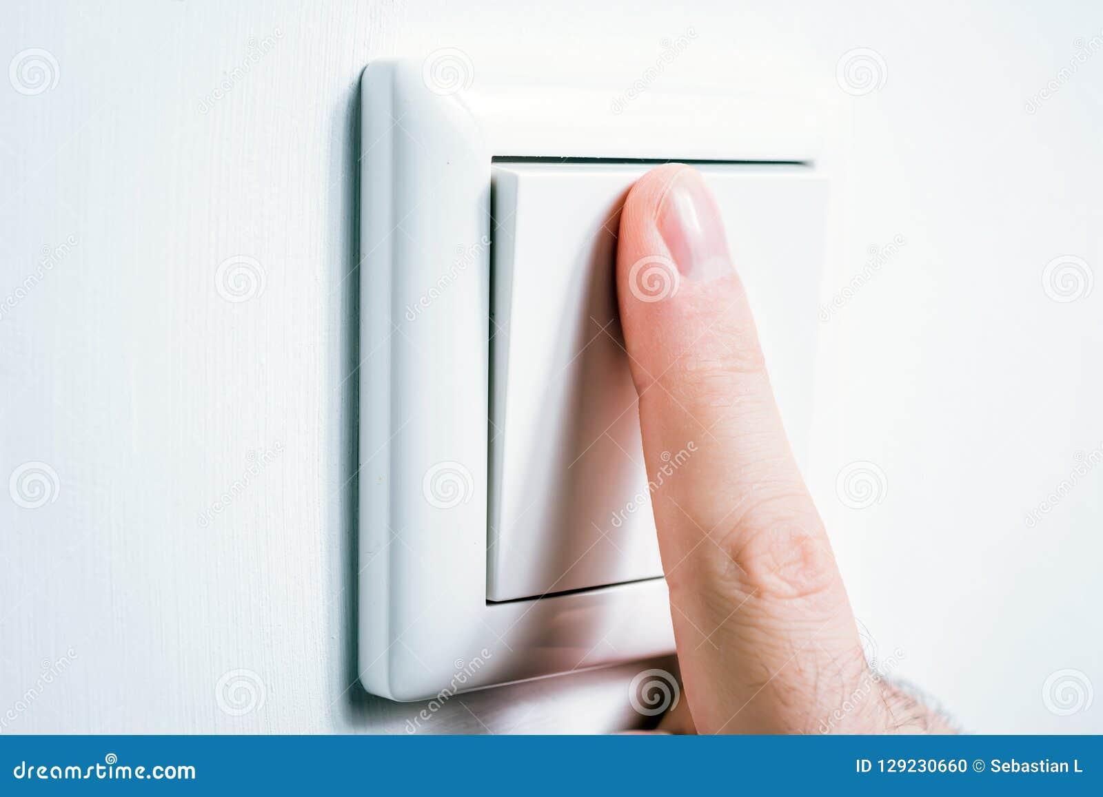 Dedo masculino que toca em um interruptor da luz para girar a luz de ligar/desligar