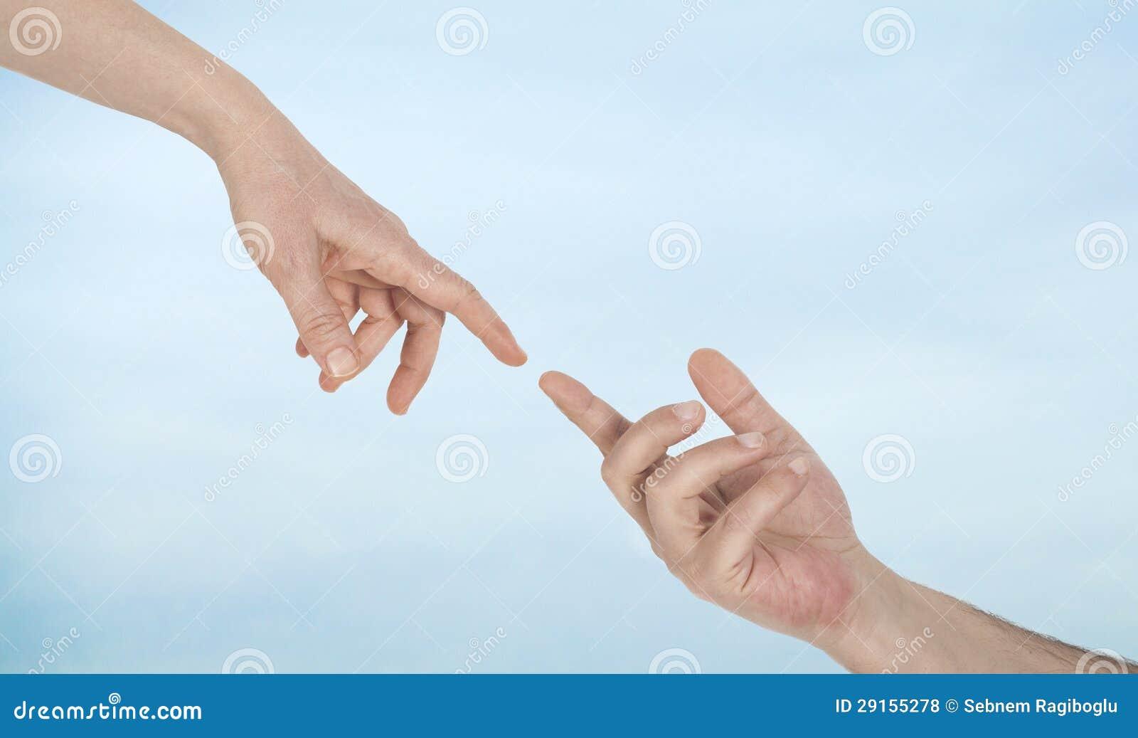 Dedos conmovedores en fondo del cielo