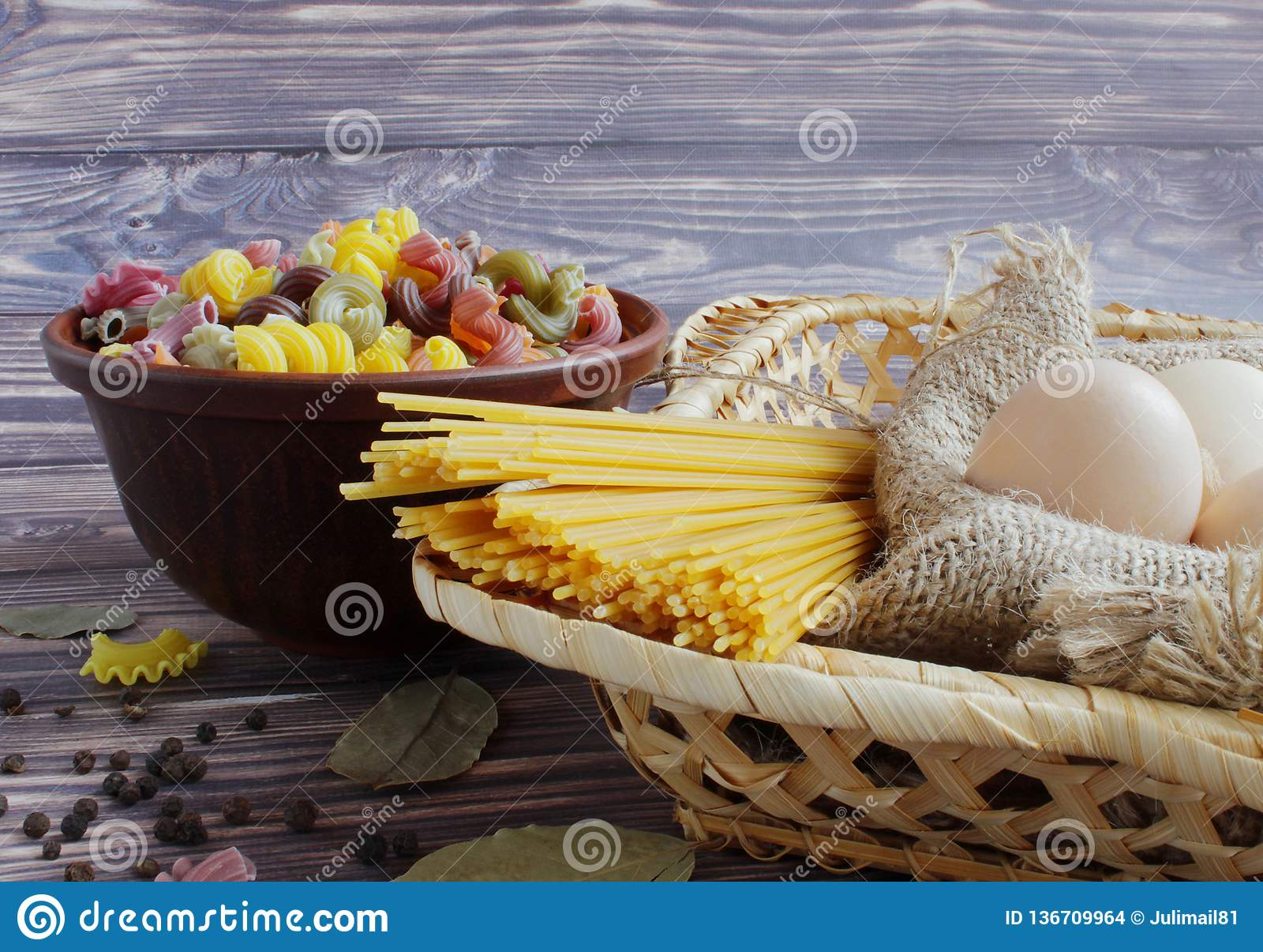 Deegwaren van verschillende kleuren, spaghetti, drie eieren, zwarte peper en laurierblad op een donkere achtergrond en een bamboe