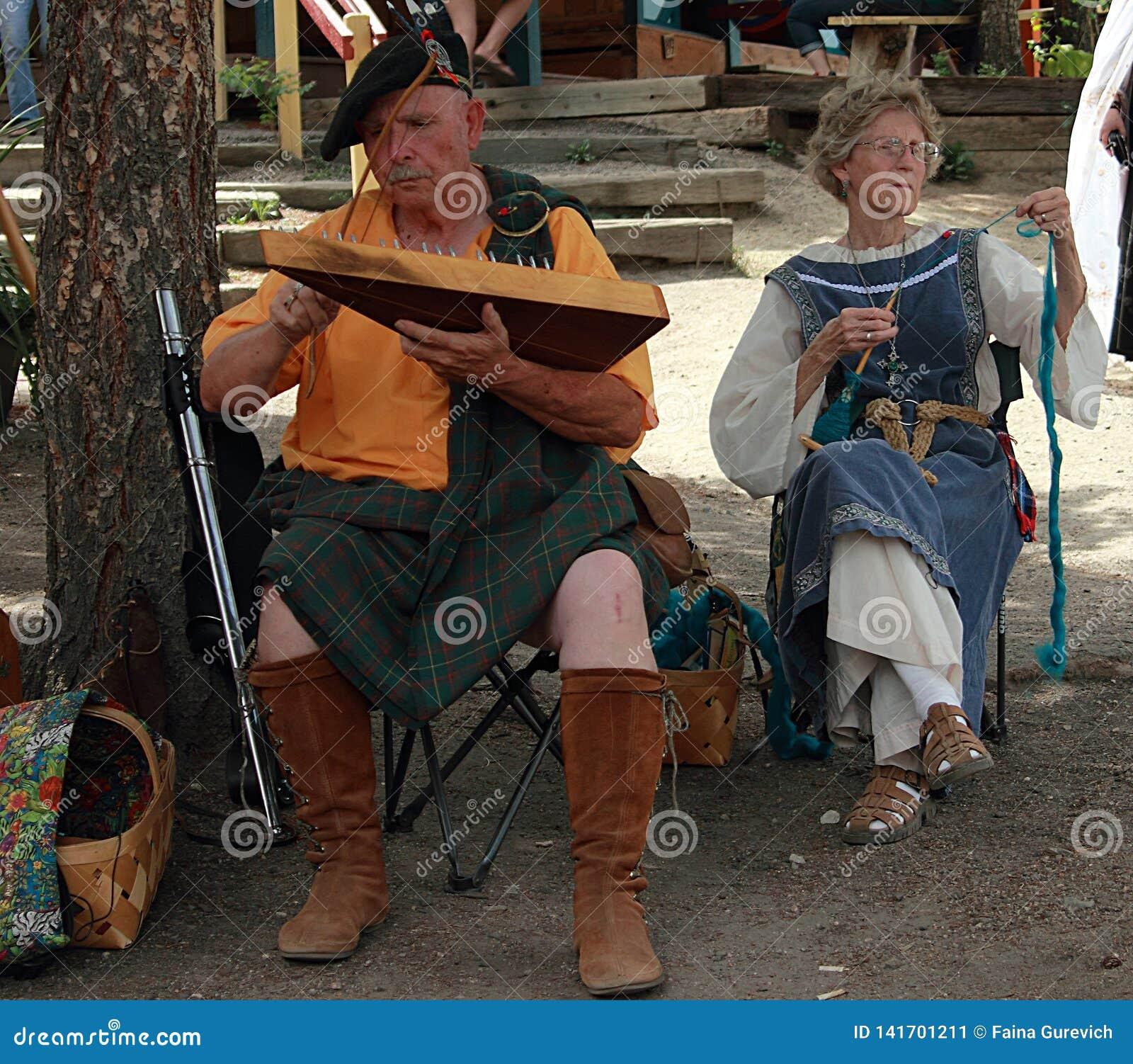 Deelnemers die typische kleren dragen die en tijdens het Jaarlijkse Renaissancefestival zingen spelen in Colorado