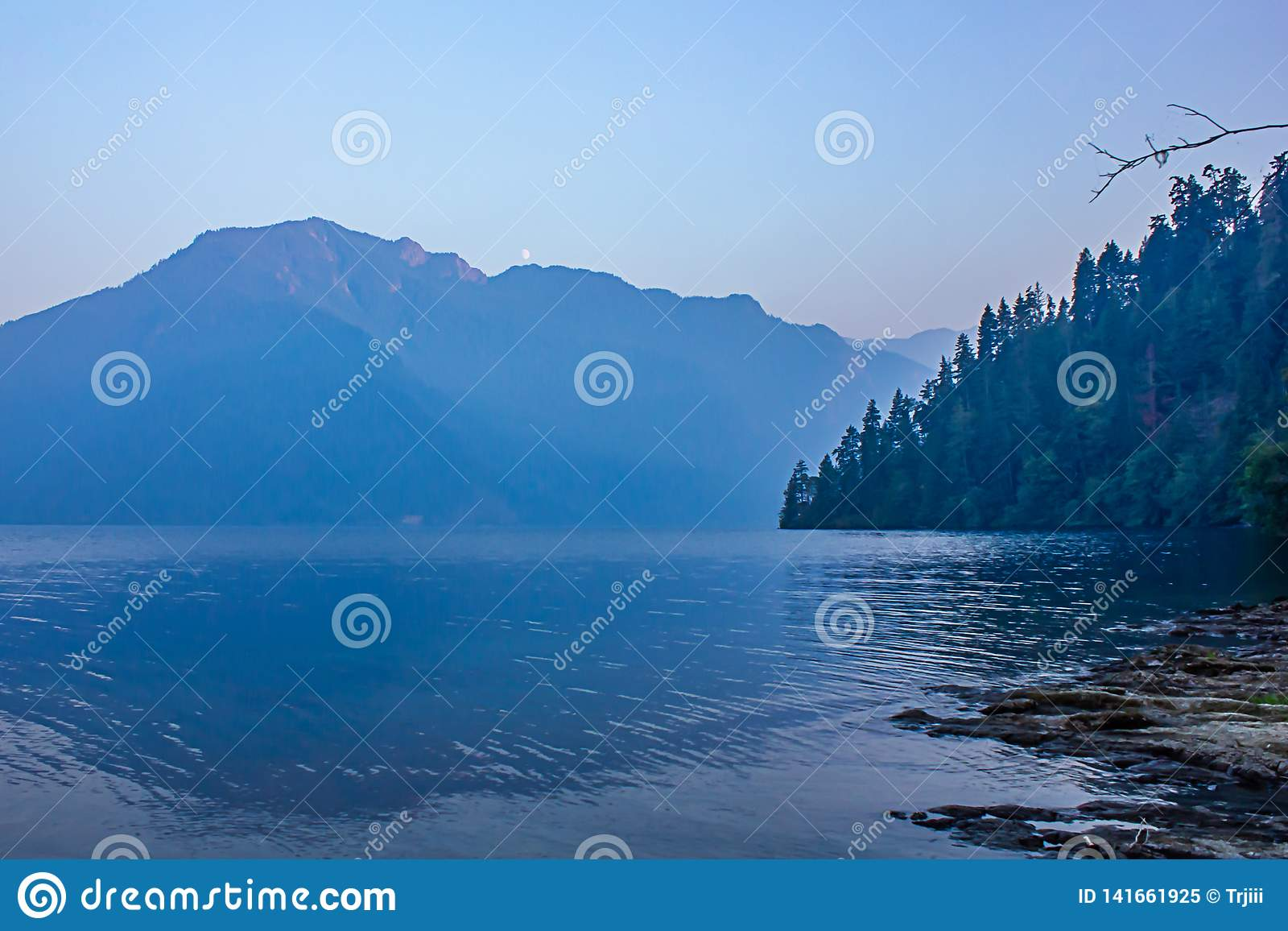 Deep blue lake at dusk in summer with mountain