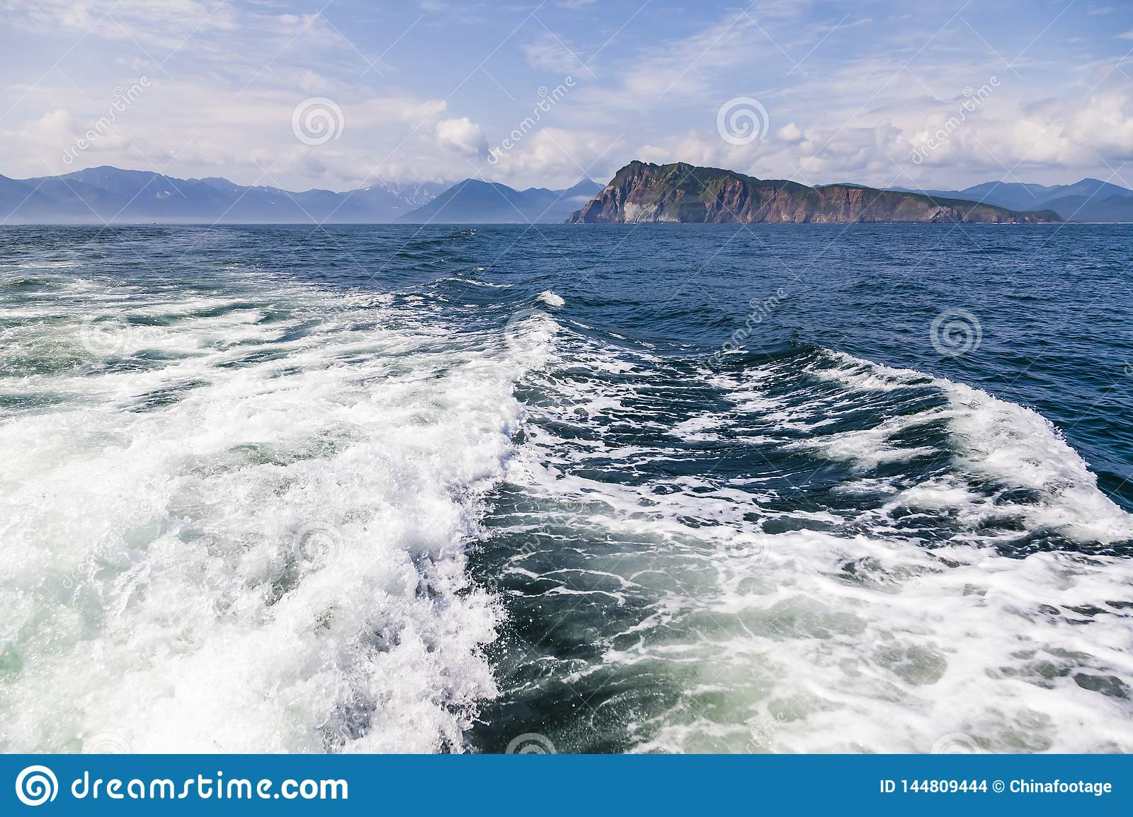A deep blue sea with island in distance with medium water wave ripple.