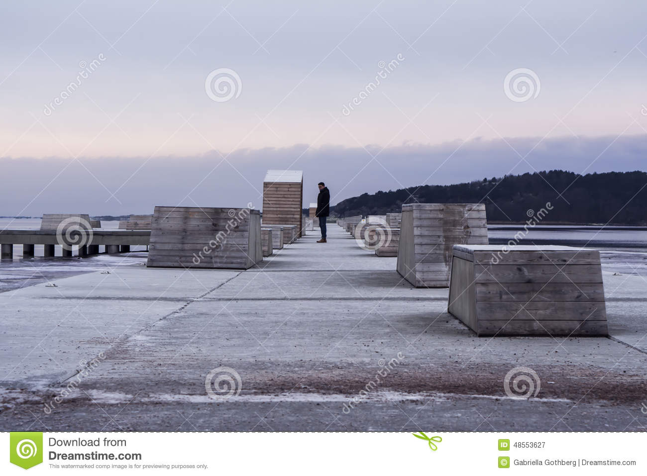 Deep perspective of a man on a pier in winter.