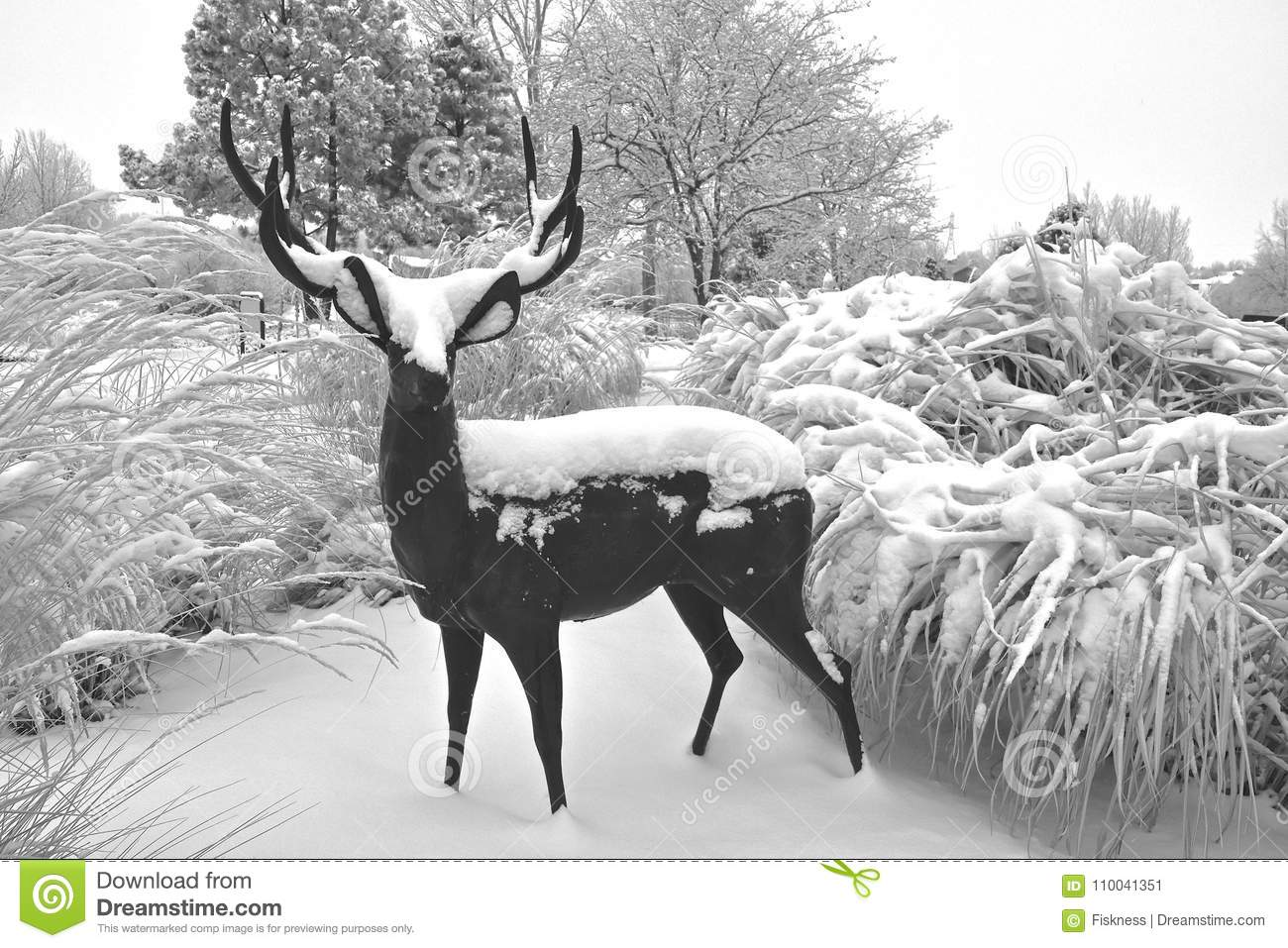 A sculpture of a deer surrounded by long grass is covered by a fresh snow black and white
