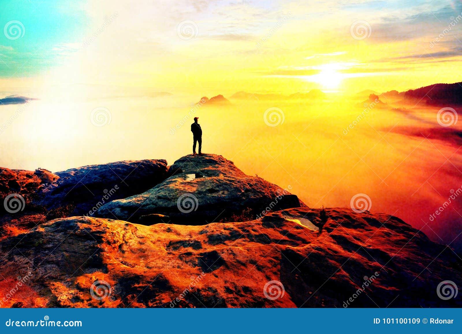 Defeito da lente Caminhante na extremidade da rocha acima do vale Equipe o relógio sobre o vale enevoado e outonal da manhã