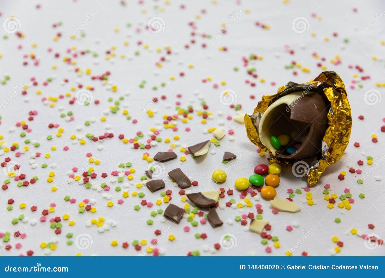 Defekte goldene SchokoladenOstereier mit bunten Schokoladen nach innen auf wei?em Hintergrund mit bunten unscharfen Konfettis
