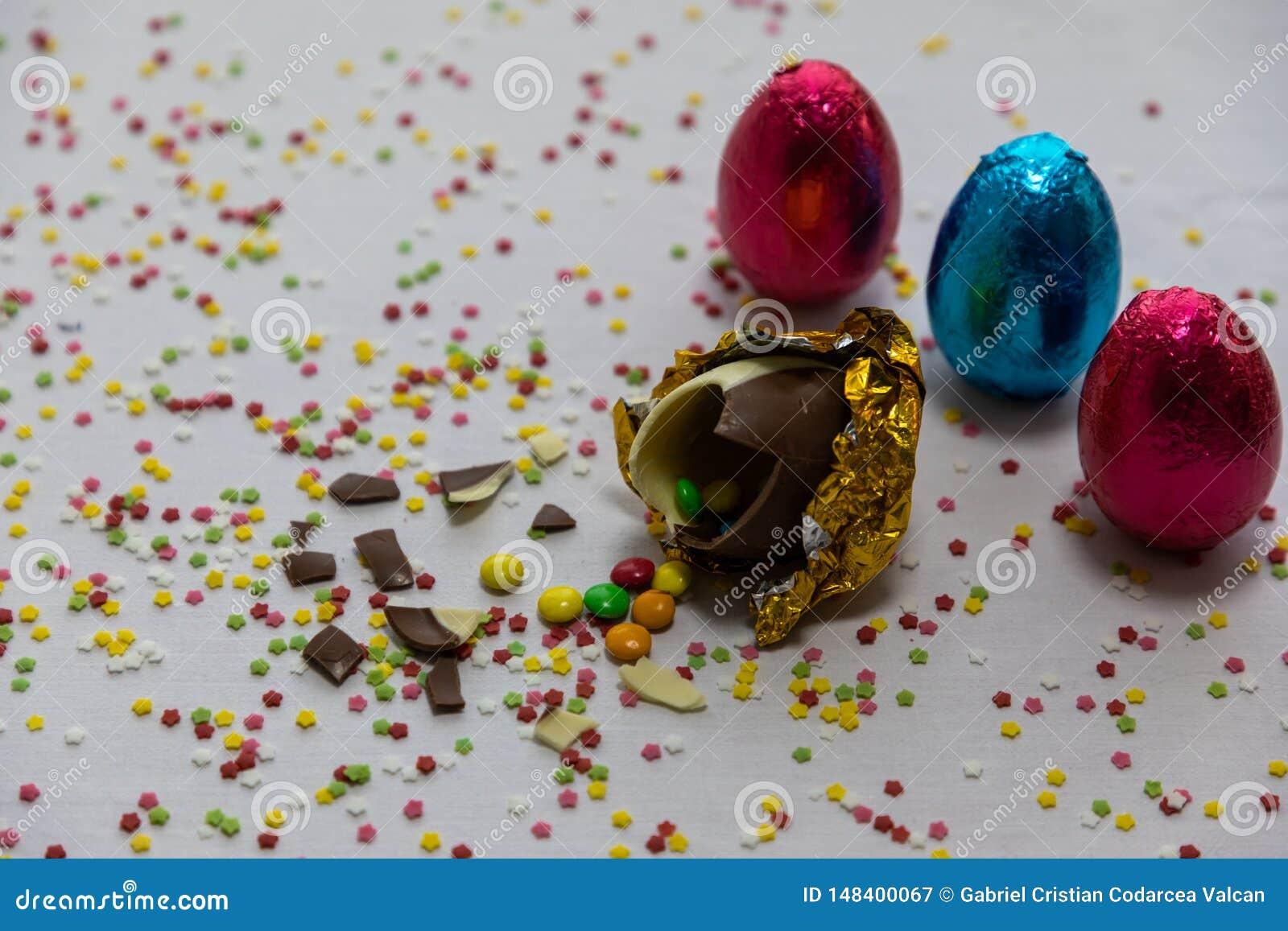 Defekte goldene SchokoladenOstereier mit bunten Schokoladen nach innen auf wei?em Hintergrund mit bunten unscharfen Konfettis und