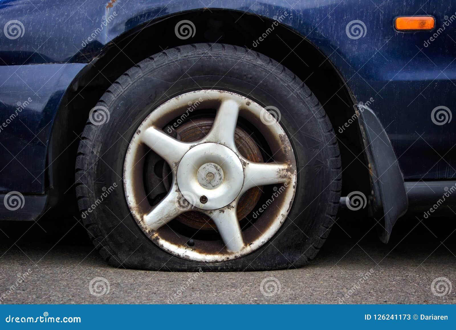 Deflaterat bilgummihjul på ett rostat hjul