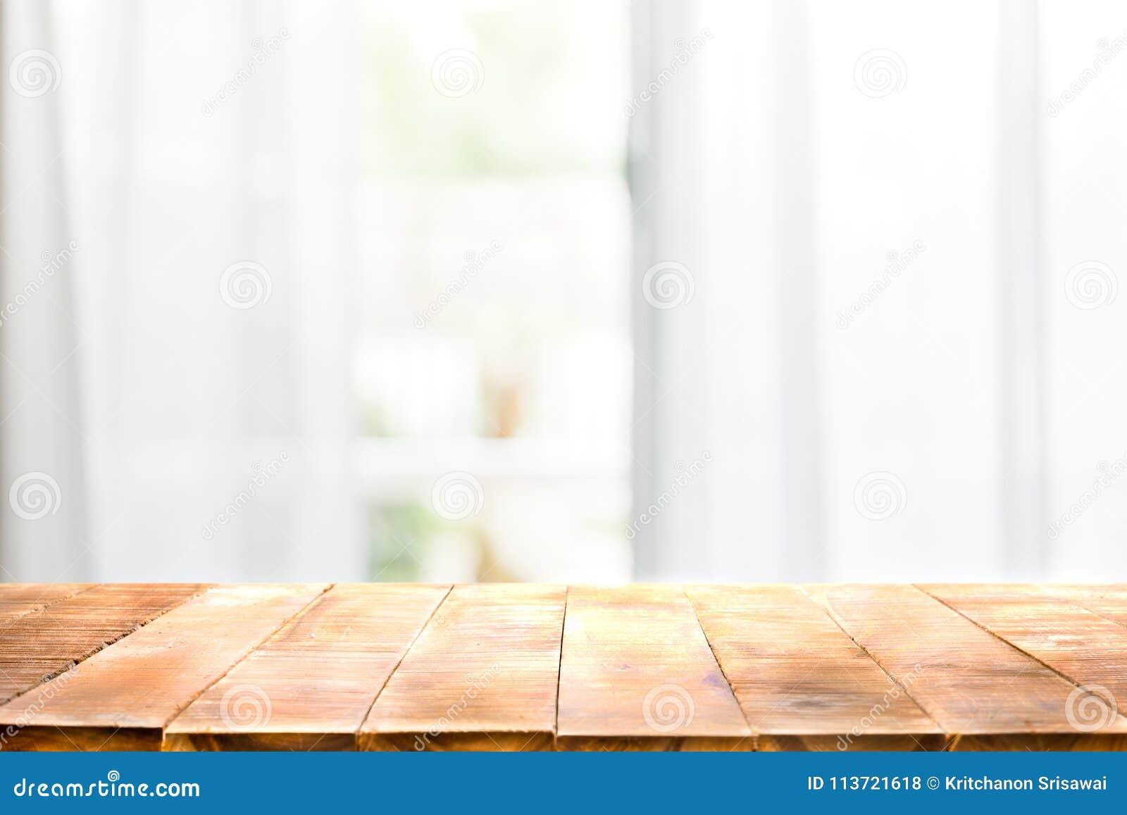 Defocused帷幕窗口和倒空与温暖的阳光的木台式