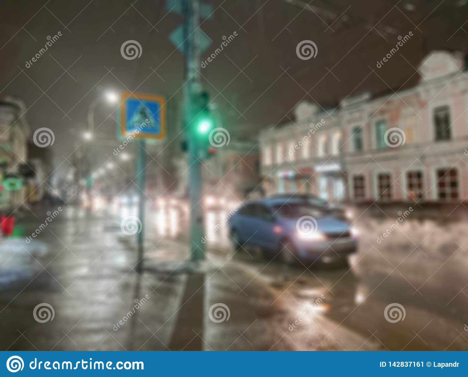 Defocused abstract image. Bokeh effect. Blurred background. Evening cityscape in rainy weather. Cars and night lights