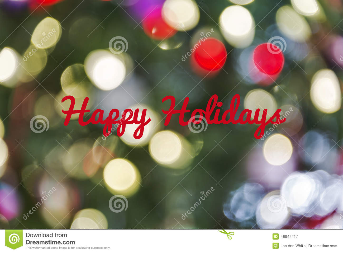 Defocused Christmas light background with Happy Holidays text
