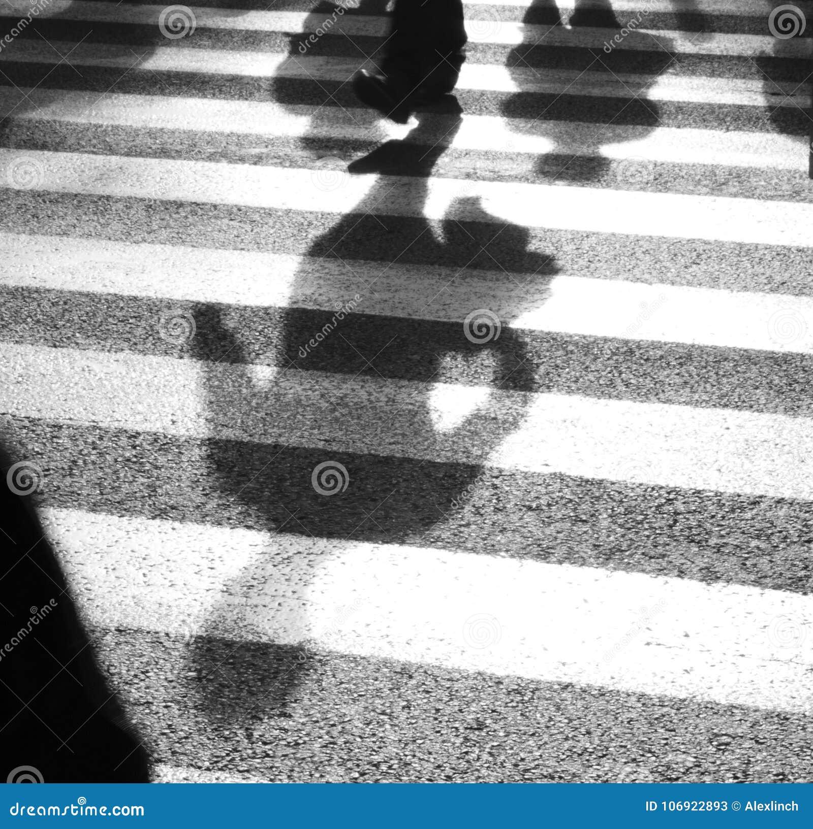 Defocused cienie pedestrians krzyżuje ulicę