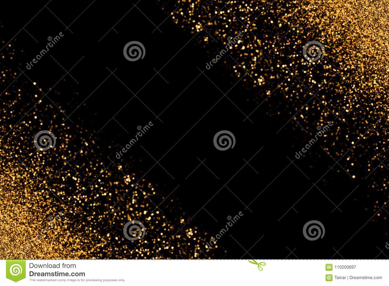 Defocused gold glitter with glowing sparks lights on a black background. Holiday greeting card