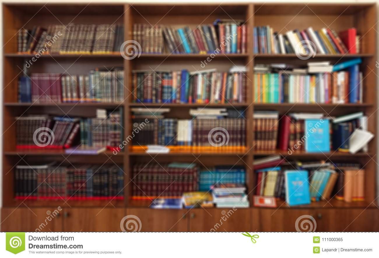 Defocused image. Multi-colored books on the bookshelf in the library. The bokeh effect