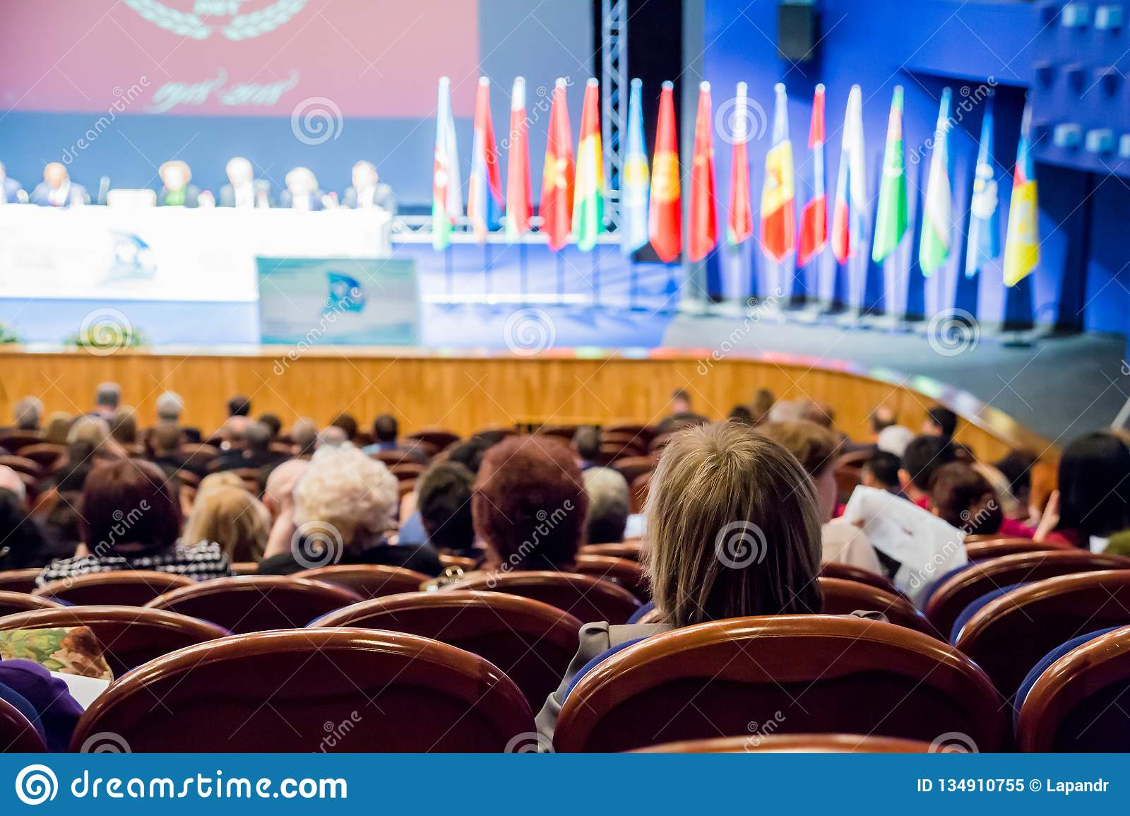 Defocused image. People in the auditorium. International conference. Flags of different countries on stage