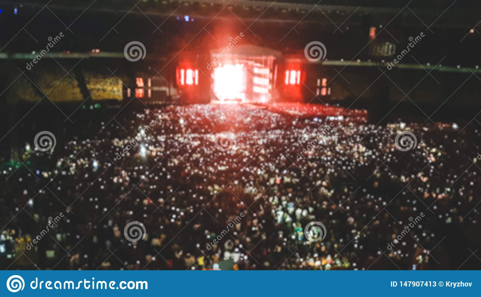 Defocused photo of big stadium full of fans on the rock music concert. Perfect backdrop for illustrating party, disco or